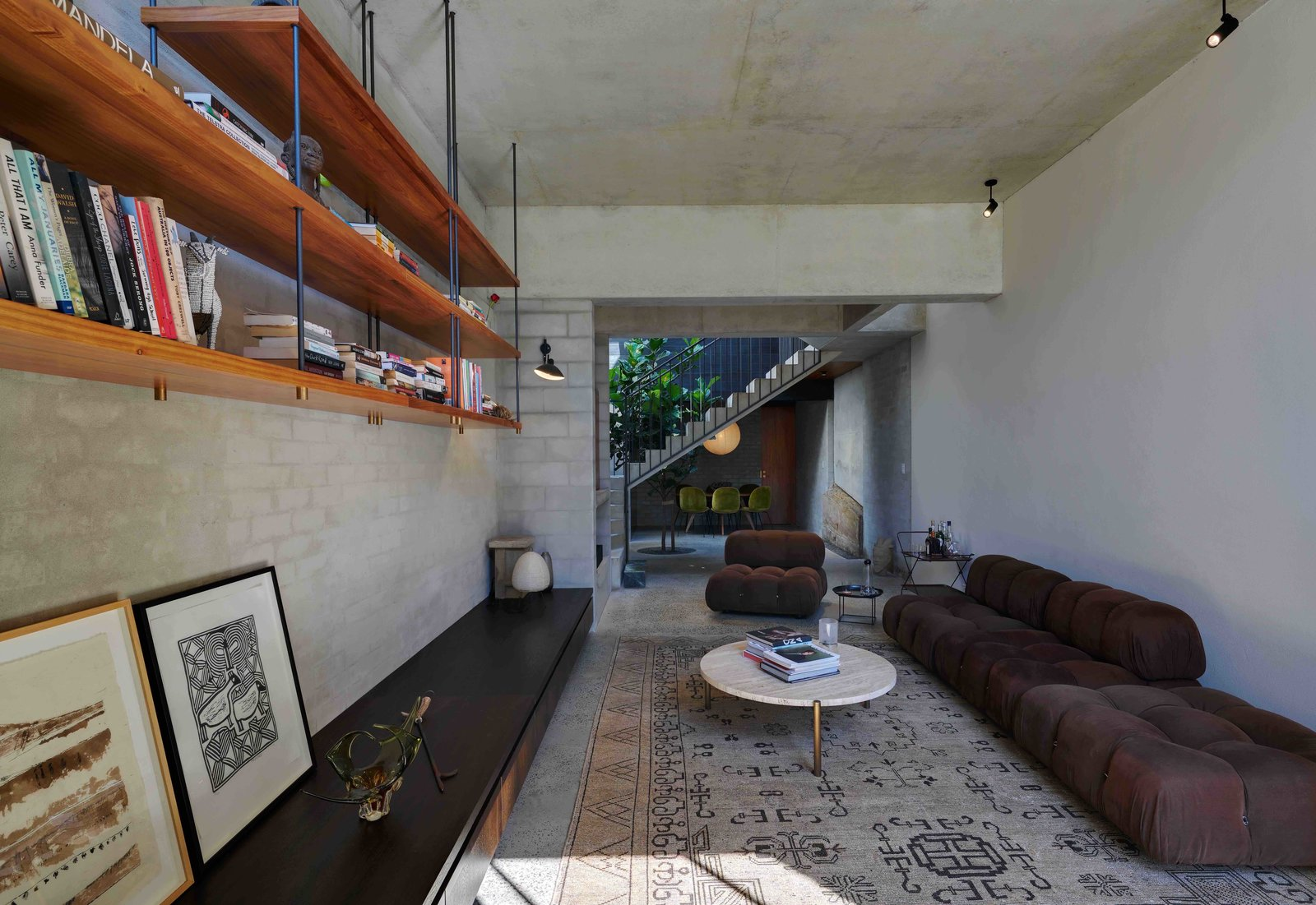 Living Room, Sofa, Chair, Coffee Tables, Shelves, Ceiling Lighting, Concrete Floor, Rug Floor, and Storage  Photo 9 of 17 in Find Out How Light and Precious Outdoor Space Were Introduced to an Old Australian Cottage