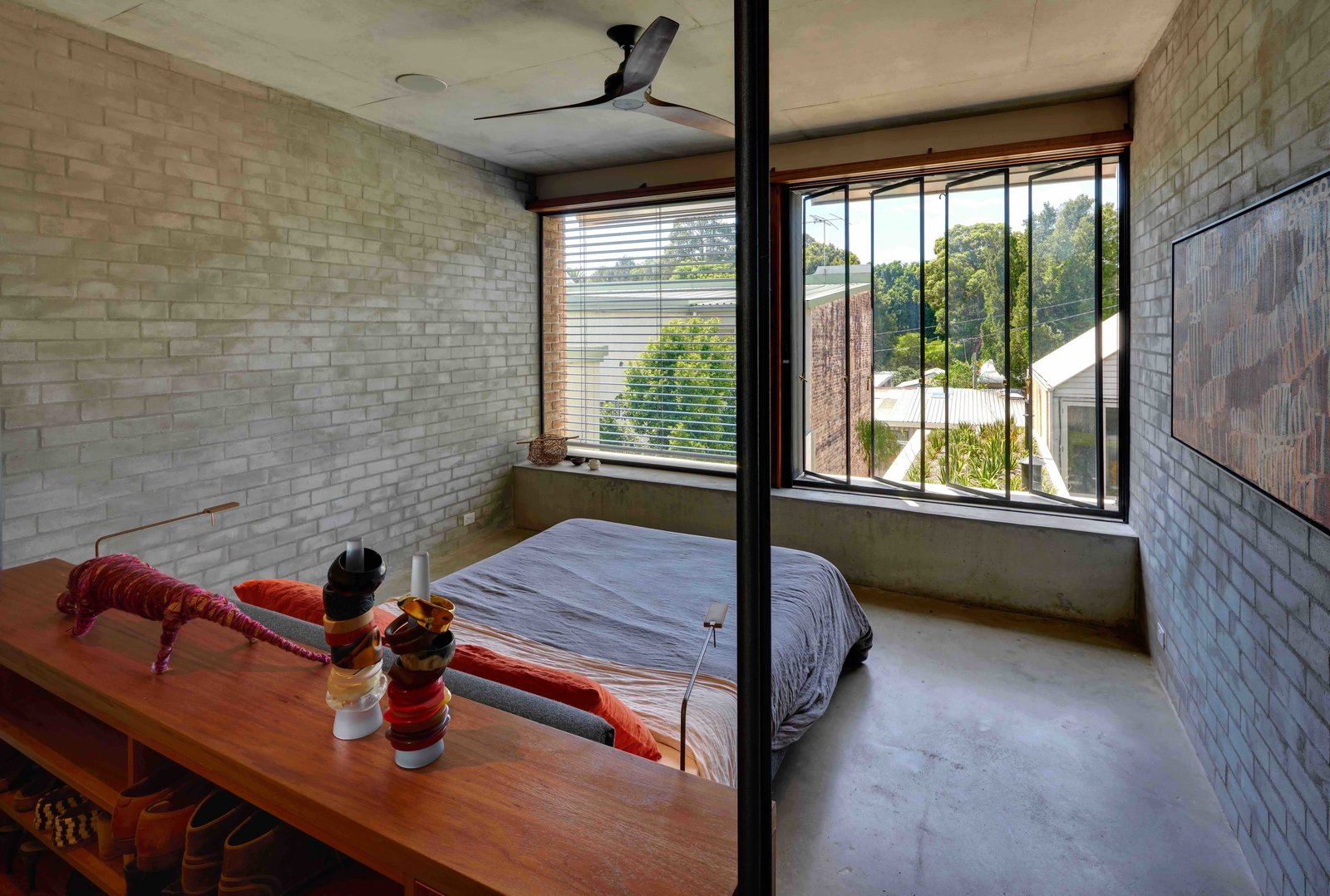 Bedroom, Bed, Storage, Shelves, Concrete Floor, and Wall Lighting  Photo 10 of 17 in Find Out How Light and Precious Outdoor Space Were Introduced to an Old Australian Cottage
