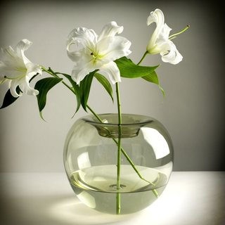 Since glass is such a contemporary material, flowers immediately take on a streamlined and modern appeal when they're paired with it. The Stamen Glass Vase by Niche Modern is one example of a minimalist, blown-glass vessel that's ideal for delicate flowers. Stick with freshly cut blooms for an elegant look.