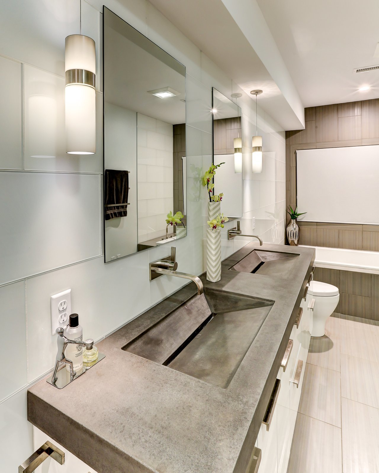 The master bathroom of this North Carolina home features very contemporary, custom made concrete countertop with integrated trough sinks.  Photo 11 of 13 in 13 Modern Bathroom Vanity Ideas
