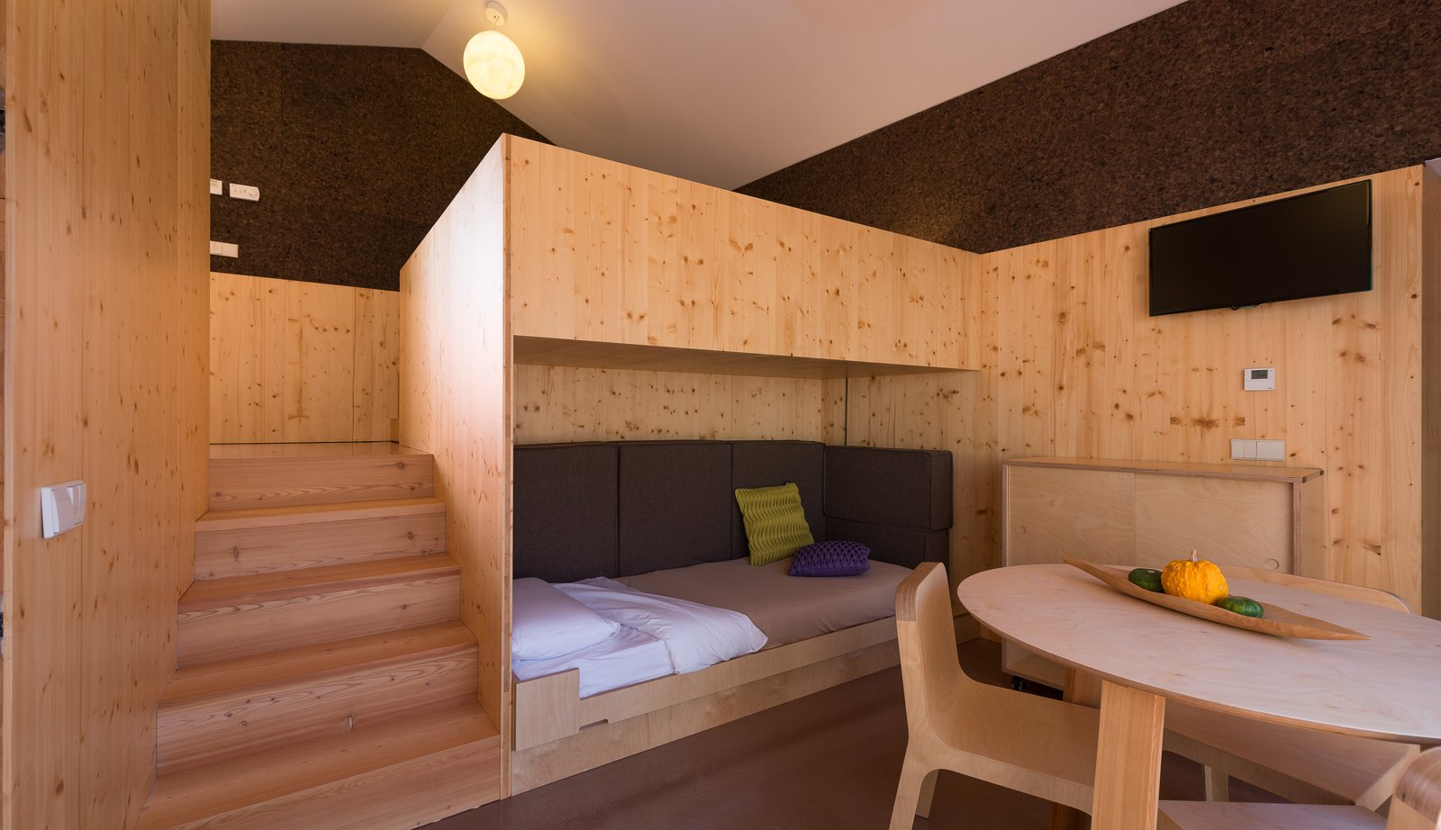 Living Room, Bench, Chair, Table, Ceiling Lighting, Storage, and Light Hardwood Floor  Photo 7 of 16 in Stay in a Tiny, Eco-Friendly House in a Portuguese Schist Village