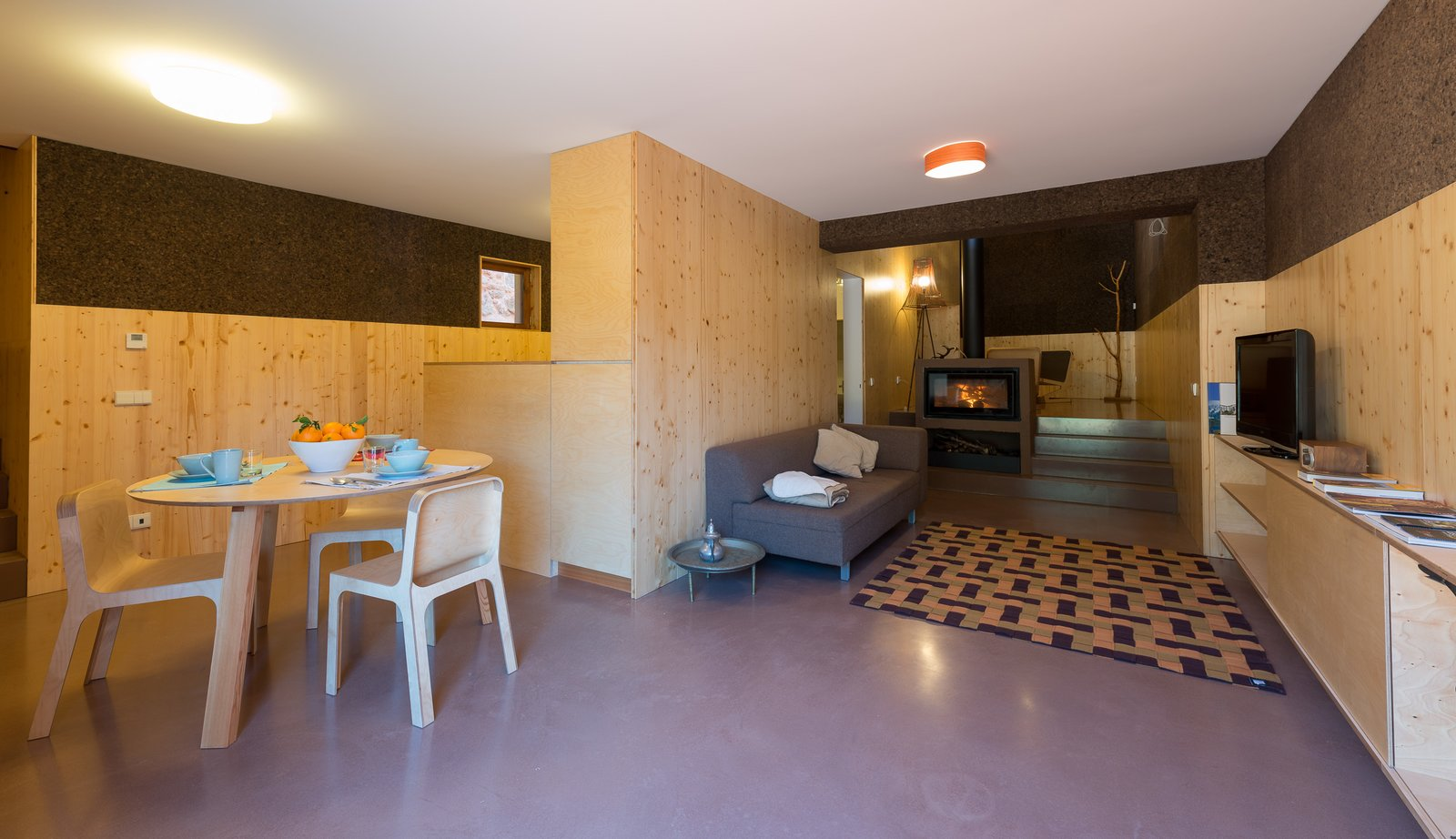 Living Room, Chair, Sofa, Sectional, End Tables, Table, Storage, Lamps, Ceiling Lighting, Floor Lighting, and Wood Burning Fireplace  Photo 9 of 16 in Stay in a Tiny, Eco-Friendly House in a Portuguese Schist Village