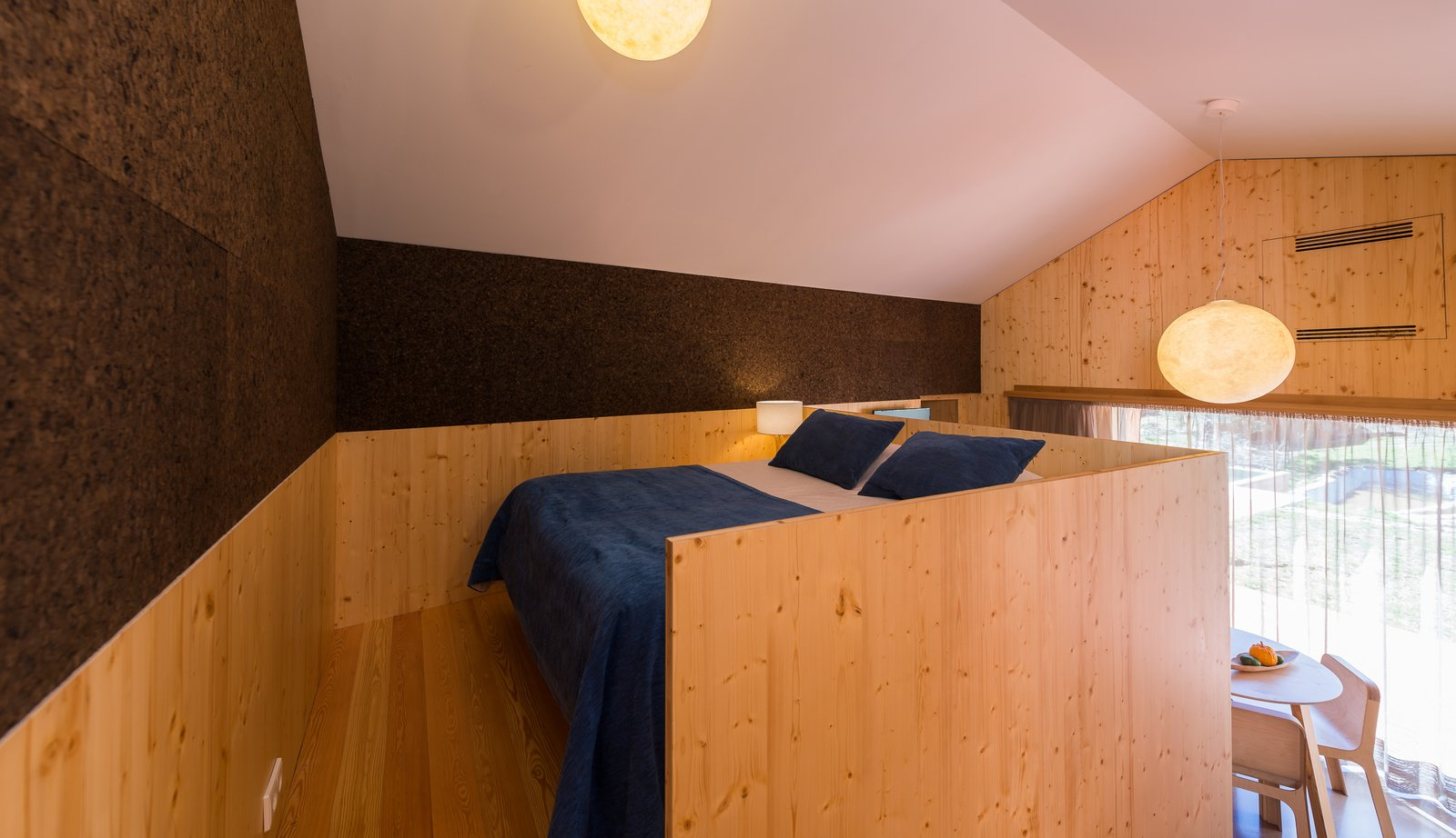 Bedroom, Bed, Ceiling Lighting, Pendant Lighting, Light Hardwood Floor, Lamps, and Table Lighting  Photo 13 of 16 in Stay in a Tiny, Eco-Friendly House in a Portuguese Schist Village