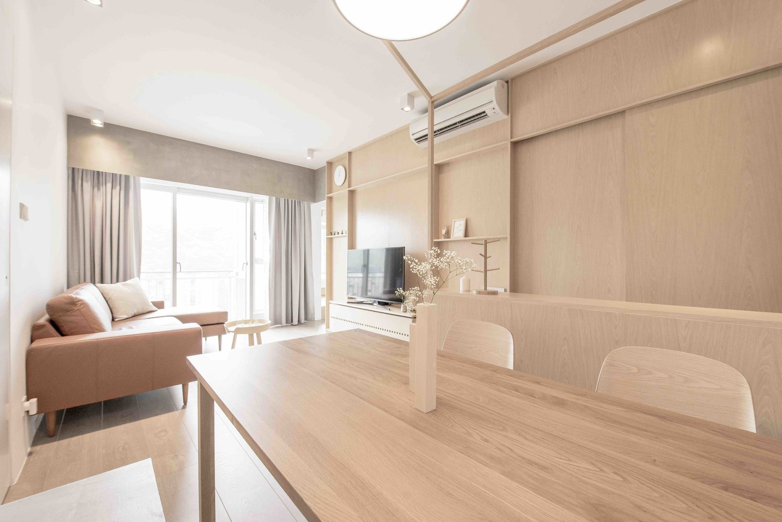 Living Room, Sofa, Chair, Sectional, Table, Ceiling Lighting, Light Hardwood Floor, and Coffee Tables  Photo 3 of 15 in An Origami-Inspired Apartment in Hong Kong With Tons of Smart Storage