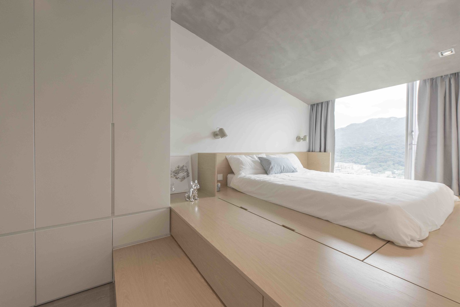 Bed, Storage, Recessed Lighting, Ceiling Lighting, Wall Lighting, Light Hardwood Floor, Storage Room, Closet Storage Type, and Under Stairs Storage Type  Photo 6 of 15 in An Origami-Inspired Apartment in Hong Kong With Tons of Smart Storage