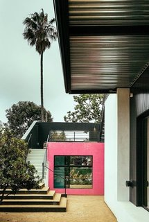 Designed by DEX Studio, this Venice Beach home has splashes of vibrant colors and large surface-mounted sliding doors that connect the interiors with the backyard and pool.
