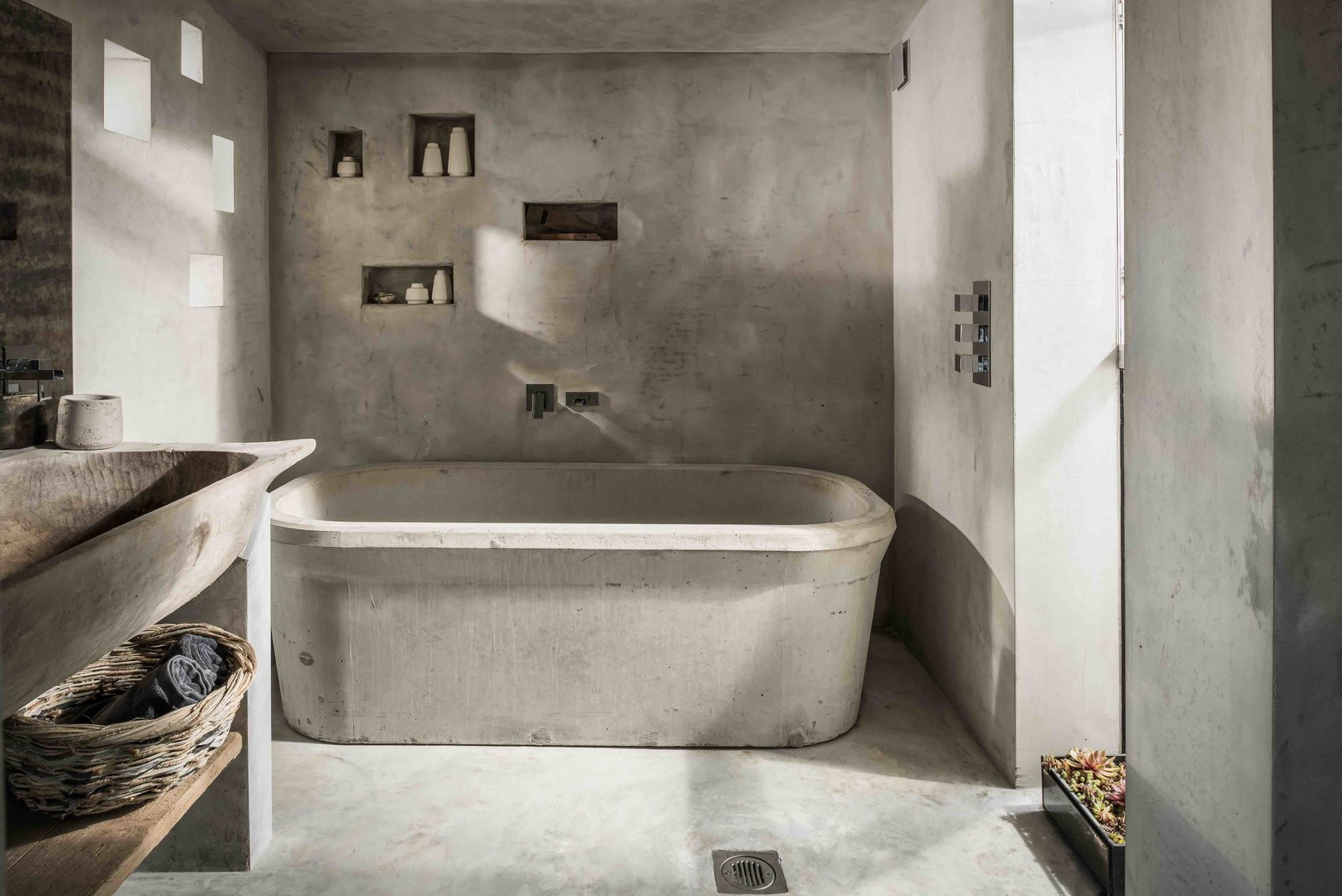 Bath Room, Concrete Counter, Concrete Floor, Concrete Wall, Pedestal Sink, and Freestanding Tub  Photo 10 of 13 in Hide Out in a Tiny Concrete-and-Shingle Cottage For Rent in Cornwall