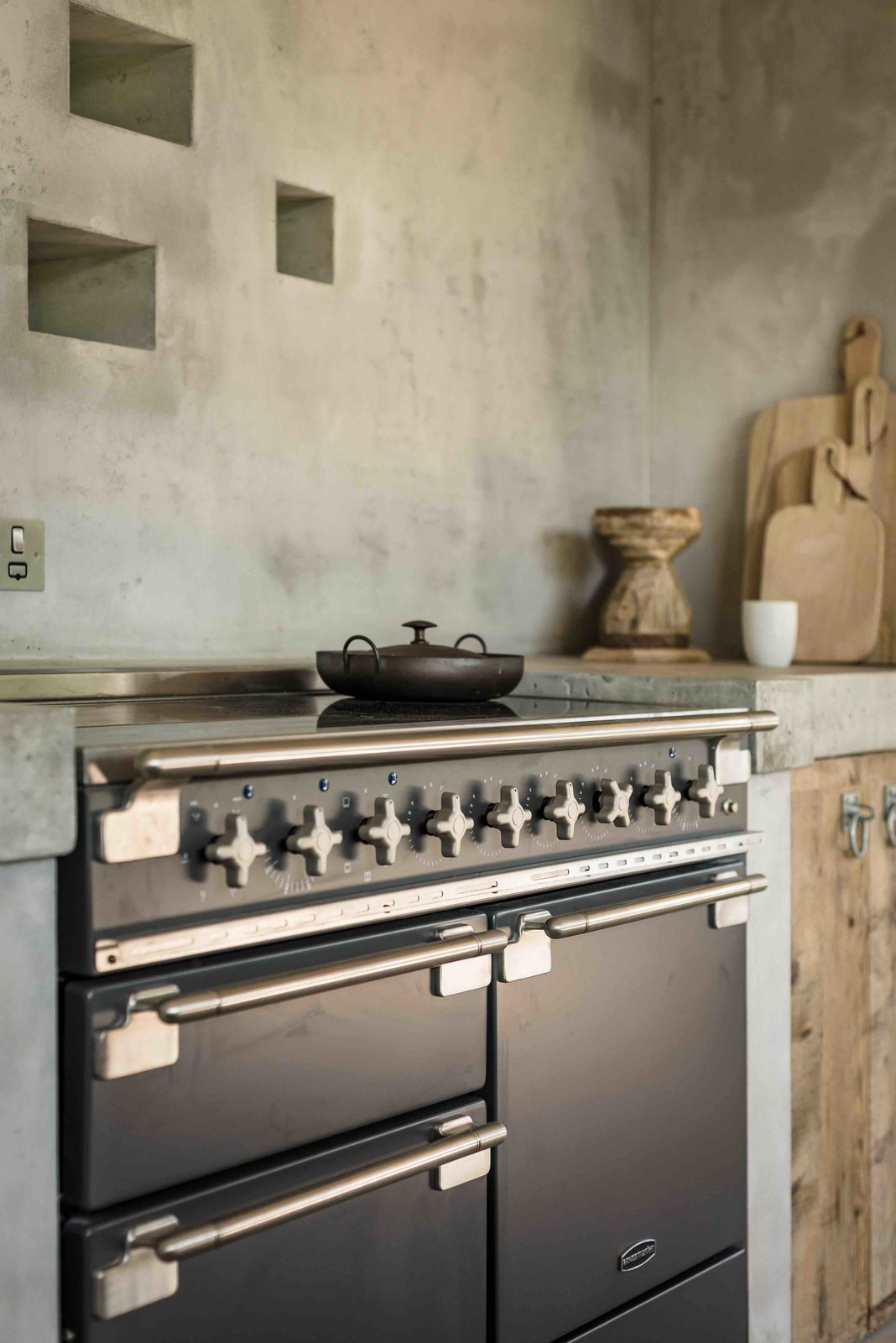 Kitchen, Concrete Counter, Wood Cabinet, Range, and Wall Oven  Photo 7 of 13 in Hide Out in a Tiny Concrete-and-Shingle Cottage For Rent in Cornwall