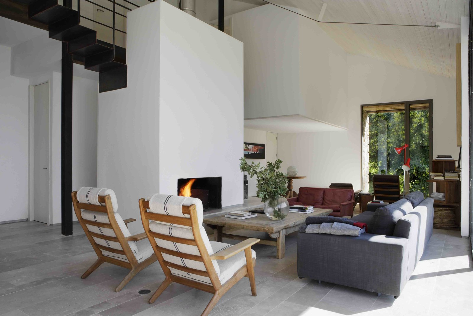 Living Room, Chair, Sofa, Floor Lighting, Standard Layout Fireplace, and Coffee Tables  Photo 4 of 14 in An Abandoned Stable in Spain Is Transformed Into a Sustainable Vacation Home For Rent