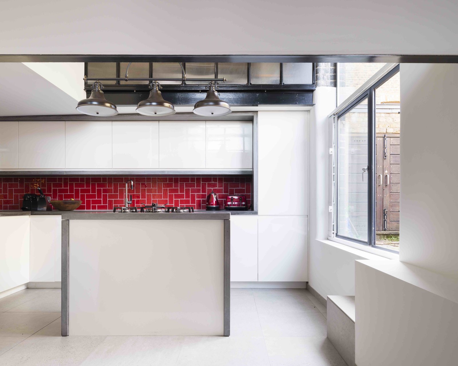 Kitchen, Concrete Counter, White Cabinet, Ceramic Tile Floor, Subway Tile Backsplashe, Pendant Lighting, Refrigerator, Range, and Drop In Sink  Photo 6 of 12 in An Old Grain Warehouse on the River Thames Is Transformed Into an Industrial-Modern Home