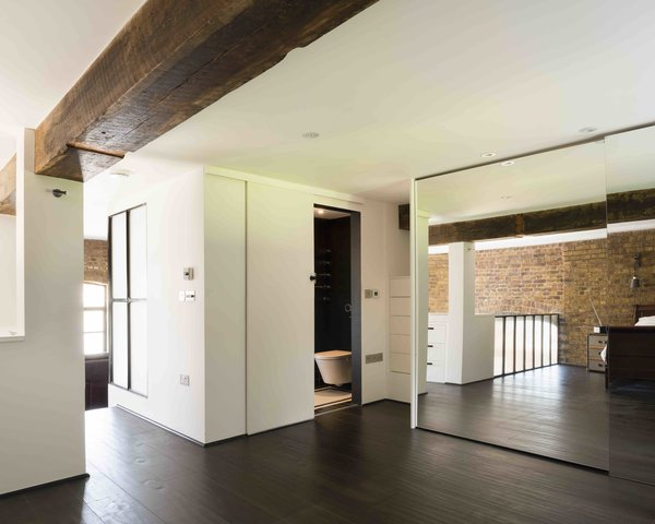 Bedroom, Dark Hardwood Floor, Ceiling Lighting, Recessed Lighting, Wardrobe, and Dresser  Photo 8 of 12 in An Old Grain Warehouse on the River Thames Is Transformed Into an Industrial-Modern Home