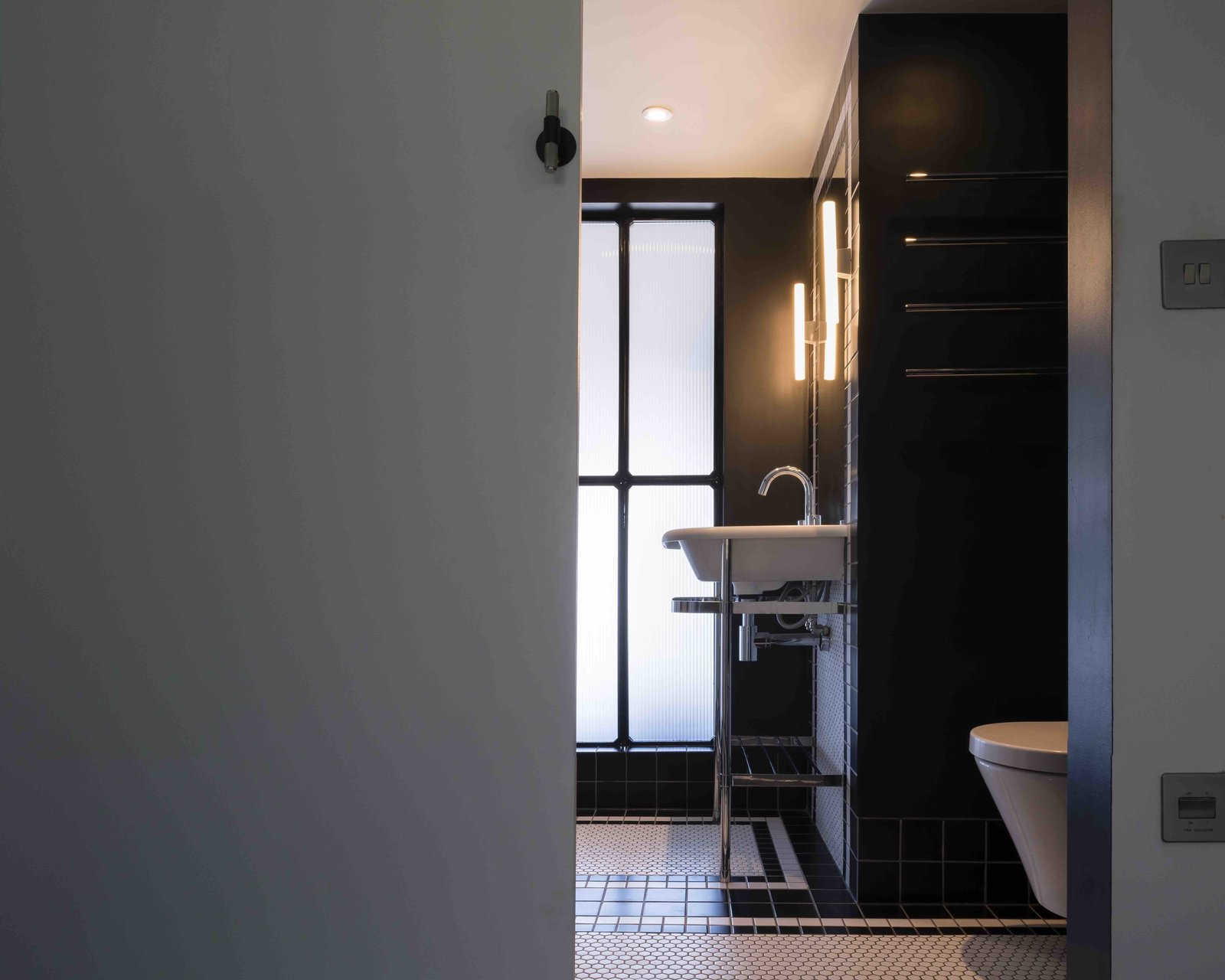 Tagged: Bath Room, Ceramic Tile Floor, One Piece Toilet, Pedestal Sink, Ceramic Tile Wall, and Wall Lighting.  Photo 9 of 12 in An Old Grain Warehouse on the River Thames Is Transformed Into an Industrial-Modern Home