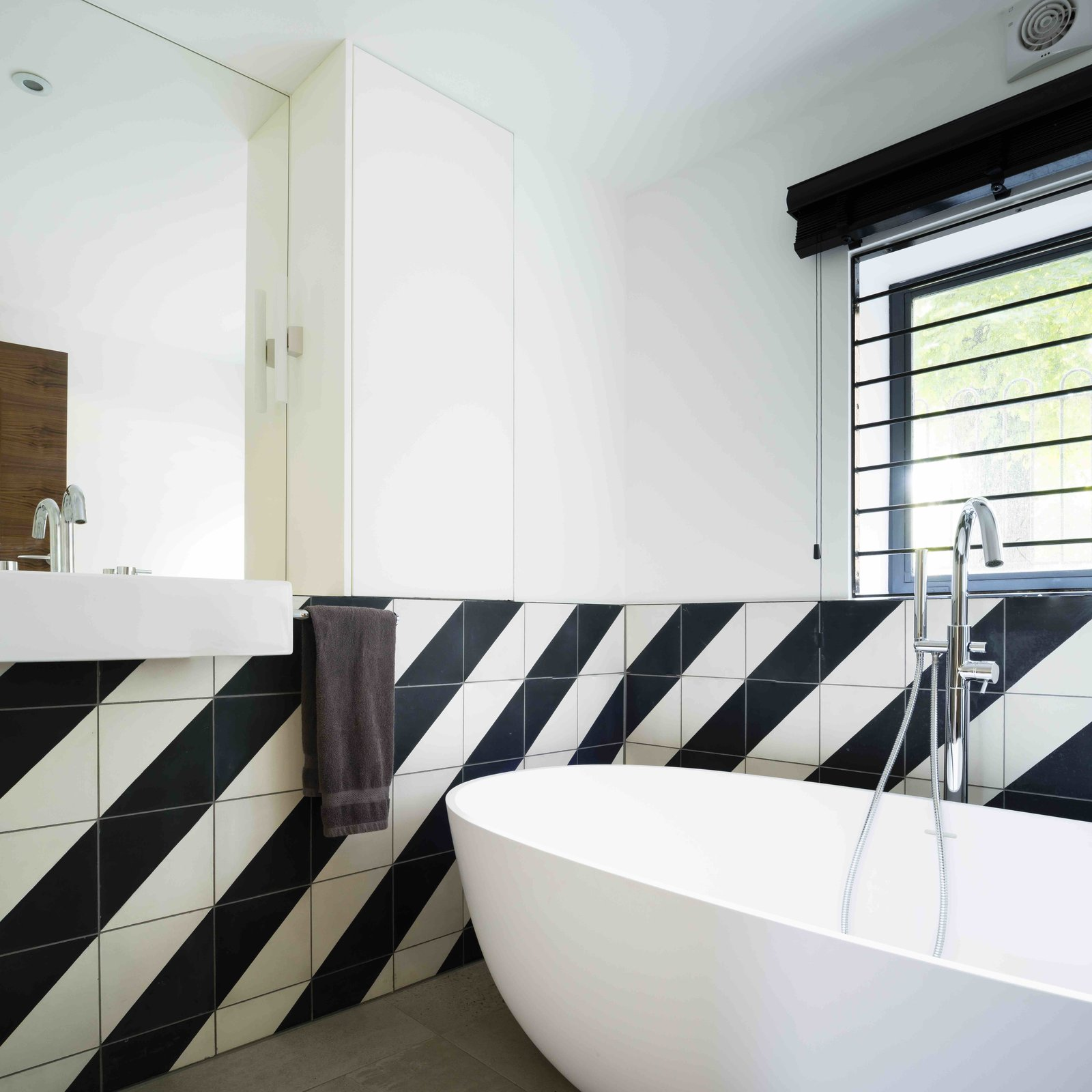 Bath Room, Freestanding Tub, Wall Mount Sink, and Ceramic Tile Wall  Photo 10 of 12 in An Old Grain Warehouse on the River Thames Is Transformed Into an Industrial-Modern Home