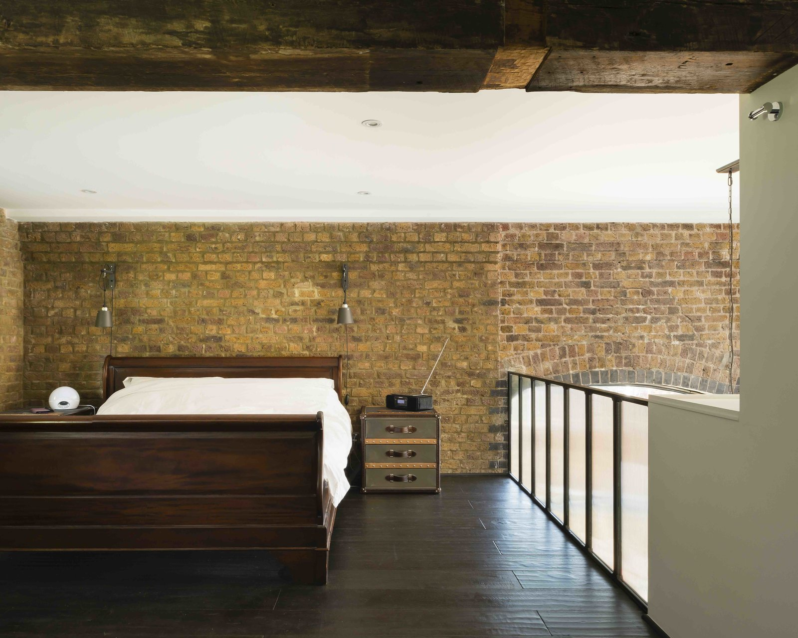 Bedroom, Bed, Night Stands, Wall Lighting, Ceiling Lighting, Recessed Lighting, and Dark Hardwood Floor  Photo 11 of 12 in An Old Grain Warehouse on the River Thames Is Transformed Into an Industrial-Modern Home