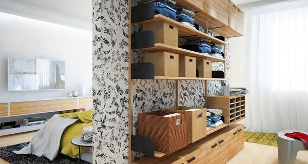 Neatly folded clothes are placed in storage baskets and shelves on this doorless wardrobe system in a small bedroom.