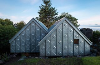 Futuristic in materials and finish but traditional in shape, this little prefab vacation retreat on the western coast of Scotland has a bold facade that's made with zinc and plywood.