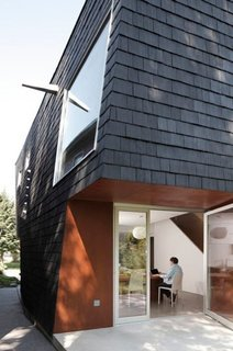 "In Buffalo, New York, architect Adam Sokol designed ""Birdhouse,"" a house with a black facade composed of shingles made out of locally recycled rubber."