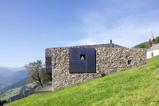 On the site of old farmhouse ruins in Italy, architecture firm Bergmeister Wolf Architekten built a new section with concrete, weathered steel, and wood shingles to contrast with the old stones.