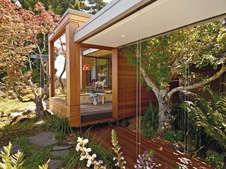 A 1950s Joseph Esherick home in Berkeley, California, was updated by its owners in 2009 to include a new Japanese-inspired pavilion composed of two prefabricated, off-center volumes beneath a butterfly roof that's half-clad with solar panels.
