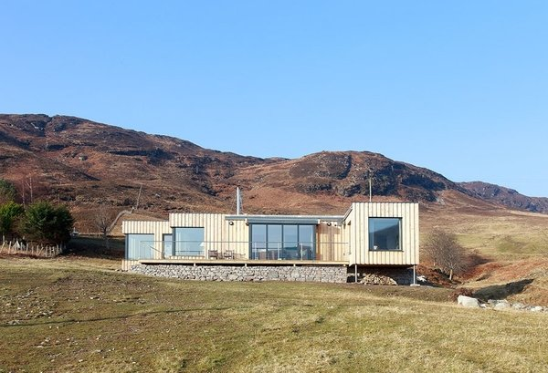 Exterior Boutique Modern rose to the challenge of building a modular prefab in a remote location in Ullepool in the Scottish Highlands. Because of the area's extreme weather conditions, the builders used thicker wall sections with added external insulation to ensure the house stays warm in winter.  Photo 7 of 8 in 7 Modern Modular and Prefabricated Homes in the UK