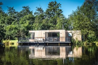 7 Prefabs Set in Nature - Photo 4 of 7 - In 14 weeks, UK prefab and modular home builders Boutique Modern completed this off-the-grid lakeside home that sits deep in Dorset's Hook Park Forest. The house draws water from the lake, and electricity is produced via solar panels and stored in a battery. Extra energy can be generated with a small diesel generator when needed.