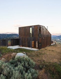 7 Prefabs Set in Nature - Photo 5 of 7 - Openess and isolation is what architect Jesse Garlick enjoys most about his off-the-grid prefabricated vacation home in the eastern Washington desert. The house has a steel facade that mimics the ochre-red bedrock in the area.