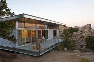 Set high in the desert of California's Yucca Valley, this hybrid prefab by Blue Sky Building Systems is constructed with an eco-friendly, light-gauge steel framing system that helps it perch lightly on the land.