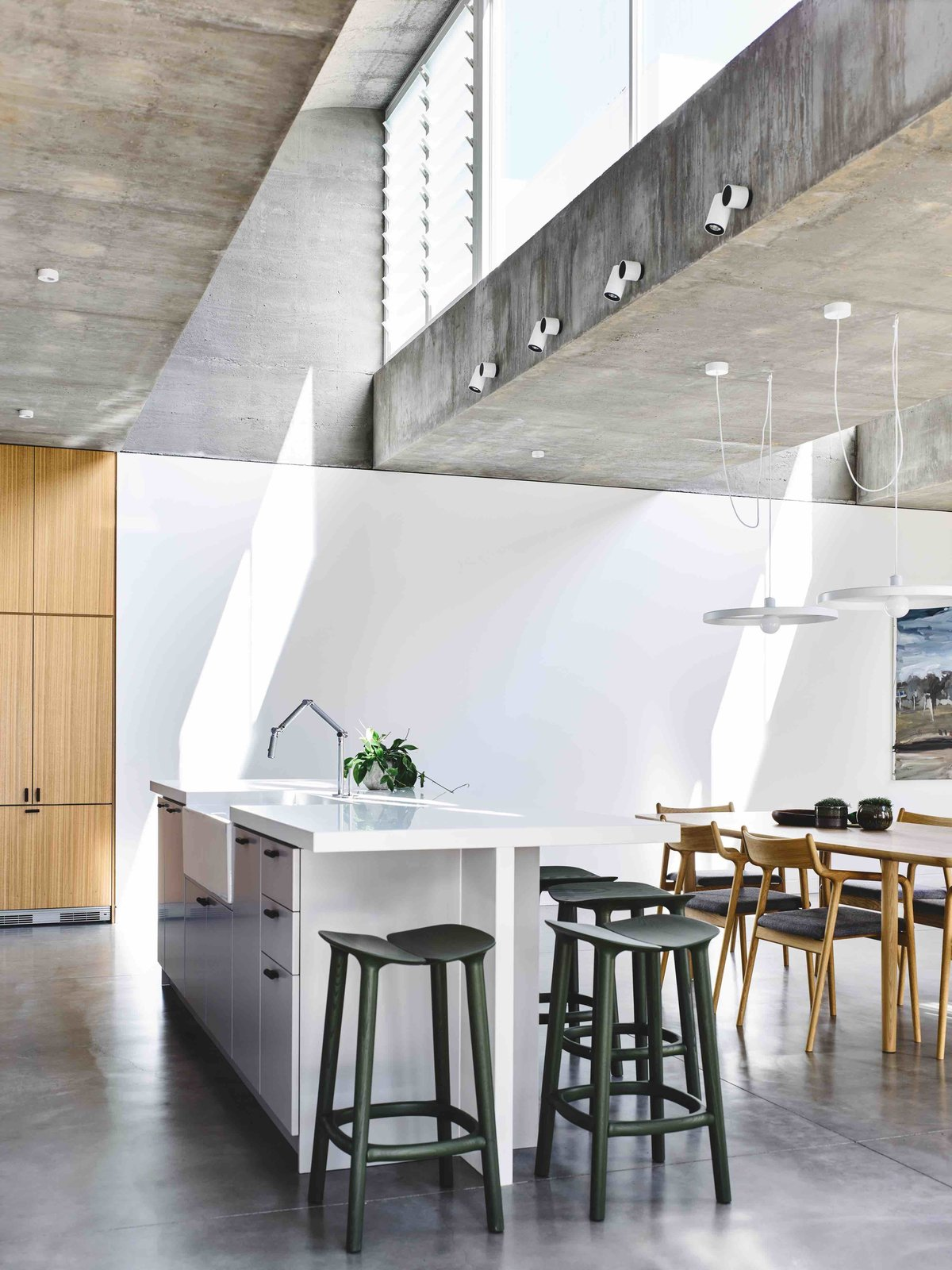 Dining Room, Bar, Stools, Accent Lighting, Concrete Floor, Chair, Table, and Storage  Photo 6 of 11 in Vaulted Skylights and Concrete Columns Connect This Melbourne Home With the Sun