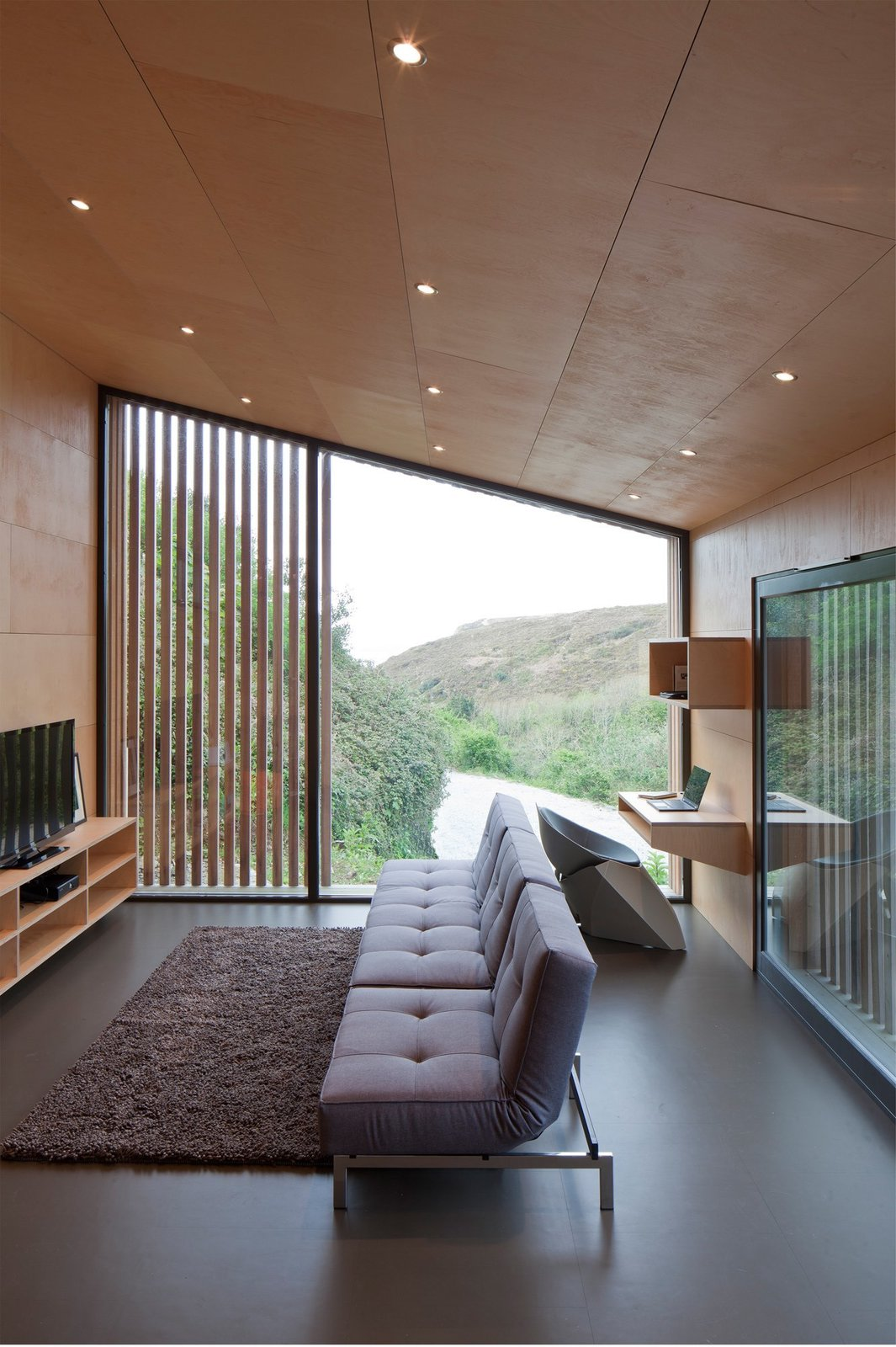 Living Room, Recessed Lighting, Sofa, Rug Floor, Desk, Chair, Shelves, and Media Cabinet  Best Photos from This Company Can Design, Build, and Deliver a Sustainable Prefab in Just 12 Weeks