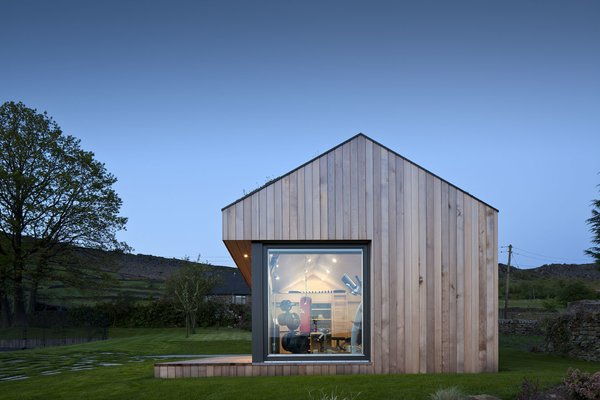 As an Ecospace with a dual-pitched roof, this gym in England's Peak District has a sloping roof, skylights that brighten and ventilate the space, and a loft-style living space.