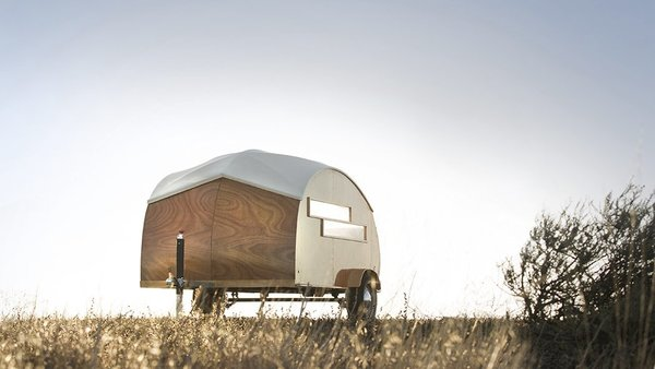 Built with modernist industrial techniques, this tiny, 44-square-foot, teardrop-shaped hybrid prefab trailer has a boat-like shell that was built with a lightweight frame enclosed with taut fabric and sheets of Jobert Okume marine plywood.