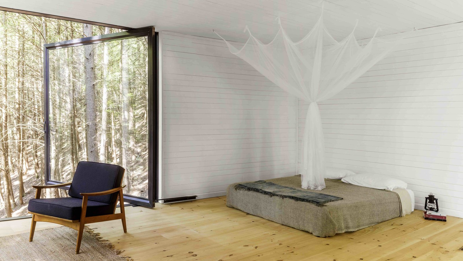 Bedroom, Bed, Chair, and Light Hardwood Floor  Best Photos from A Dramatic Tree House by Budget-Conscious DIY Builders