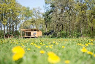 Overlooking a peaceful meadow in the province of Overijssel in the Netherlands is a snug, 452-square-foot prefabricated wooden hut with large windows that blur the boundaries between indoor and outdoor spaces. Build in two modules that were transported and assembled on site, the house, which was constructed mainly with Oregon pine, arrived complete with bathroom, kitchen, couches, table, inner walls, cabinets, beds, and floors. Custom-designed furniture, such as a sofa integrated into a sunken living area, and a U-shaped corner bench, imbues this little hut with plenty of quirky charm.