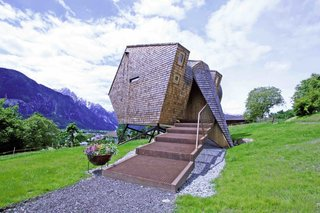 This striking split-level prefab located next to an old farmhouse in the East Tyrolean village of Nussdorf, Austria, appears to be part bird, part UFO. Designed by architects Peter and Lukas Jungmann, the 485-square-foot space, which accommodates up to eight people, is clad in rustic, Austrian-style shingles, but its sharp angles and asymmetrical shape give it a distinctly futuristic, nest-like look. Its interiors are fitted with waterproof and rot-resistant larch wood and expansive, angled-glass windows that bring in much sunlight during the day while presenting spectacular alpine views.