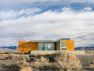 "Set in a Las Vegas desert, this prefabricated prototype designed by architect Peter Strzebniok was constructed in sections which were transported, then assembled on site. The house is composed of two complete units with interlocking sections that are raised above the ground to create a clean-lined geometric wood paneled structure of a deep gold color. Within, a ""T"" shaped floor plan encompasses three bedrooms, and a large living, dining, and kitchen area that connects to a spacious deck."