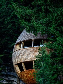 Located in the woods of Malborghetto Valbruna in the Italian Dolomite commune of Tarvisio, this egg-shaped tree house appears to hover in midair like a giant pinecone.