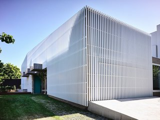 9 Best Homes With Interesting Screened Facades - Photo 1 of 18 - Designed by Melbourne practice Architects EAT, this house in the Melbourne suburb of Kew is wrapped in a screen of white aluminum slats, which gives the house structural clarity.