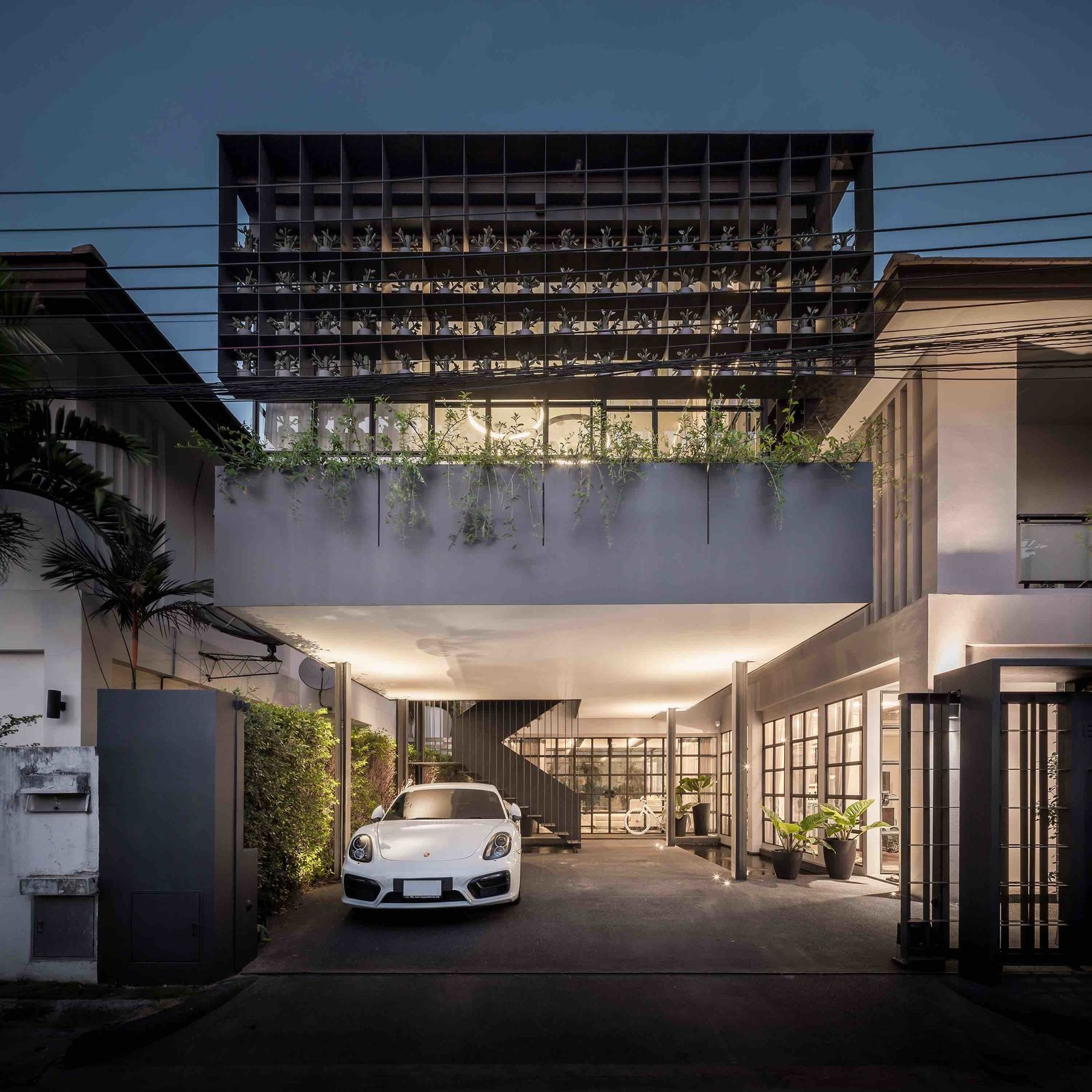 102 potted olive plants sit in the nooks of this reinforced gridded-steel framework that wraps around the front of this Bangkok home designed by Thai architecture firm Anonym Studio.  Photo 12 of 19 in 9 Best Homes With Interesting Screened Facades