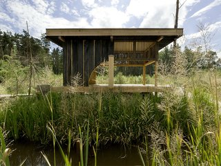 Named after its charred-larch cladding, this tearoom designed by Czech studio A1 Architects sits next to a lake in a wooded area near Česká Lípa, Czech Republic. Its sliding doors can be opened for enhanced connectivity with the surrounding nature, or closed to create a more secluded oasis. At the center of the space is a hearth that has a teapot suspended from the sisal rope-domed ceiling above it.