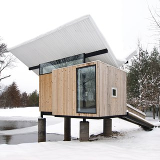 In Champaign, Illinois, this cedar hut by architect Jeffrey Poss was built as a raised platform that's accessed via a ramp. Inside are grass tatami mats, a miniature tea cabinet in a tokonoma alcove, and an oversized window that frames views of the trees.