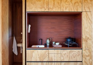 In this kitchen alcove in a New Zealand cabin, oiled jarrah eucalyptus contrasts with a kitchen niche made of plywood that's been stained reddish-brown.