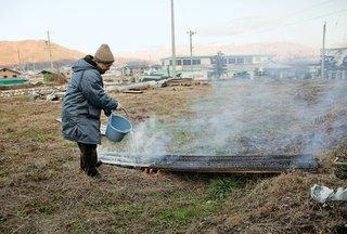Japanese architect Terunobu Fujimori pours water to cool the boards.