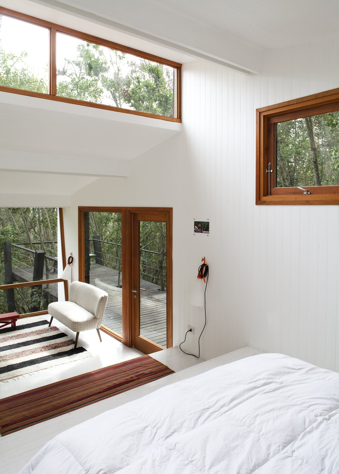 Bedroom, Bed, Painted Wood Floor, Wall Lighting, and Rug Floor  Photo 5 of 10 in A Little Chilean Tree House That's One With the Canopy