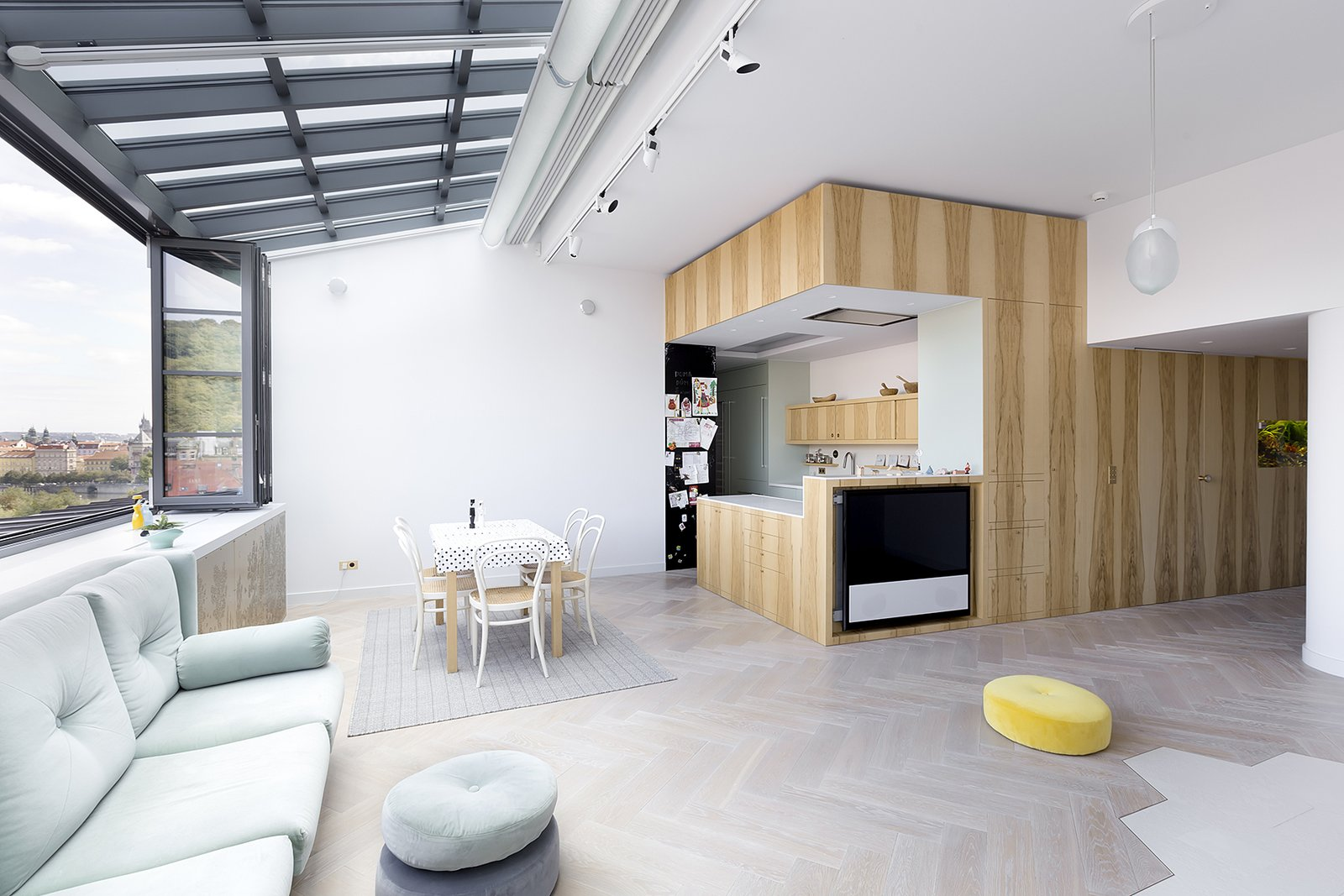 Living Room, Sofa, Light Hardwood Floor, Pendant Lighting, Track Lighting, Wall Lighting, Rug Floor, Chair, Table, and Ottomans  Photo 3 of 18 in A Dreamy Loft in Prague With Castle Views and an Onyx Moon