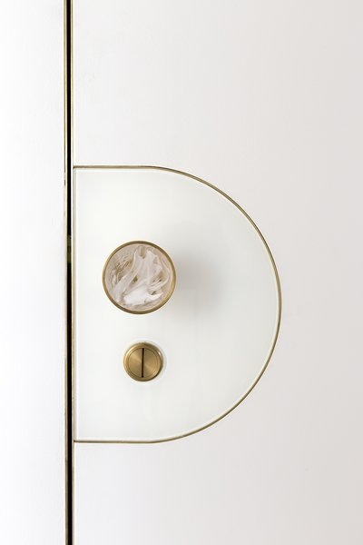 The owner of this Prague apartment splits his time between Japan and the Czech Republic, and these two design influences are reflected in the detailing. Klára Šumová, who designed the furniture and fittings, and Michaela Tomišková of Dechem, who designed the glass items and lighting, worked with A1 Architects to create brass fixtures, chandeliers, and doorknobs and handles with glass infills crafted by skilled Czech glassblowers.  Photo 12 of 18 in A Dreamy Loft in Prague With Castle Views and an Onyx Moon