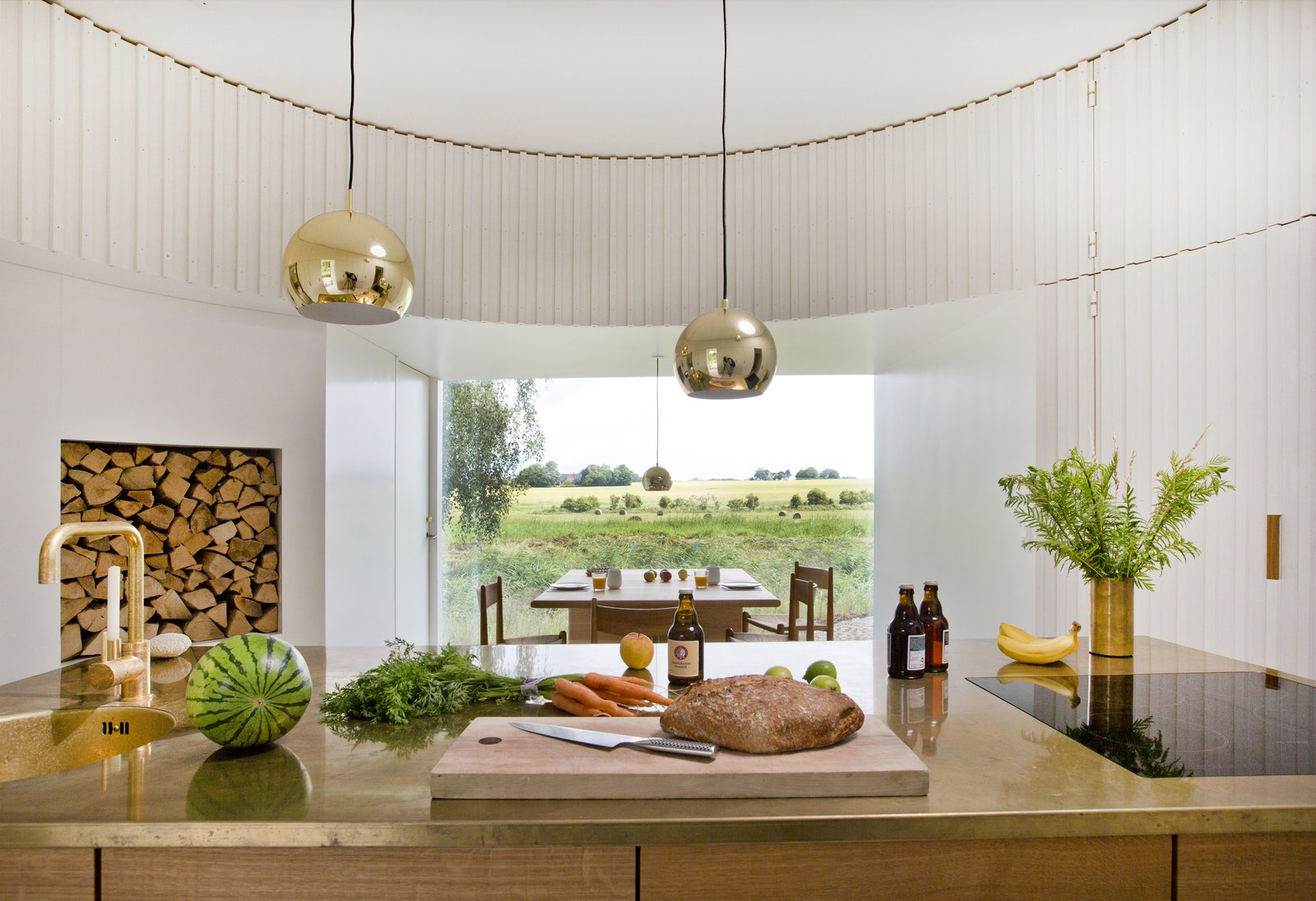 Kitchen, Metal Counter, Pendant Lighting, Wood Cabinet, Drop In Sink, and Cooktops  Photo 7 of 15 in Stay in This Danish Vacation Home Made Up of 9 Log-Clad Cylinders