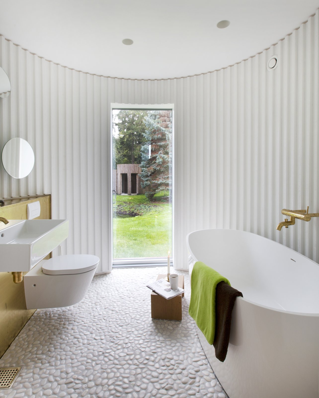 Bath Room, Wall Mount Sink, Freestanding Tub, Soaking Tub, Recessed Lighting, One Piece Toilet, and Metal Counter  Photo 11 of 15 in Stay in This Danish Vacation Home Made Up of 9 Log-Clad Cylinders