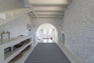 Within this minimalist villa on the Greek island of Nisyros are vaulted ceilings, arched doorways, wood beams, white-washed walls, and clean, contemporary furnishings in white, taupe, cream, and coffee tones.