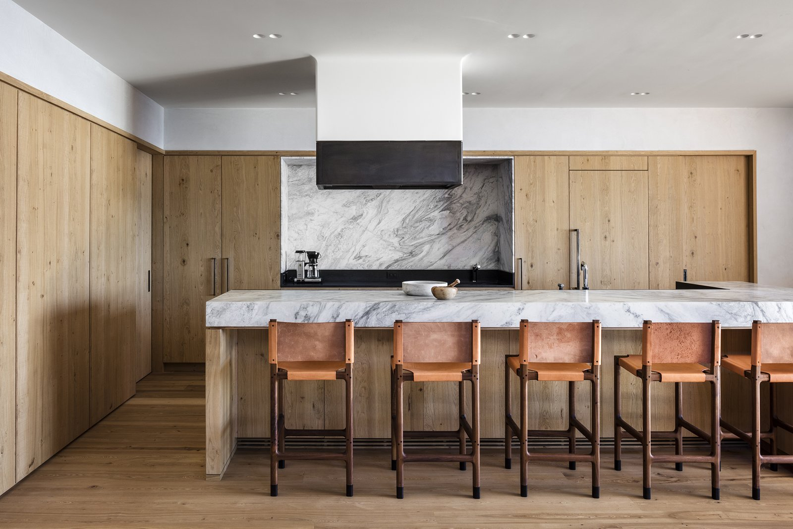 Kitchen, Marble Counter, Range Hood, Light Hardwood Floor, Marble Backsplashe, Wood Cabinet, and Recessed Lighting  Photo 9 of 13 in An Incredible Cedar-Clad House Captures Views of the Sea and Forest