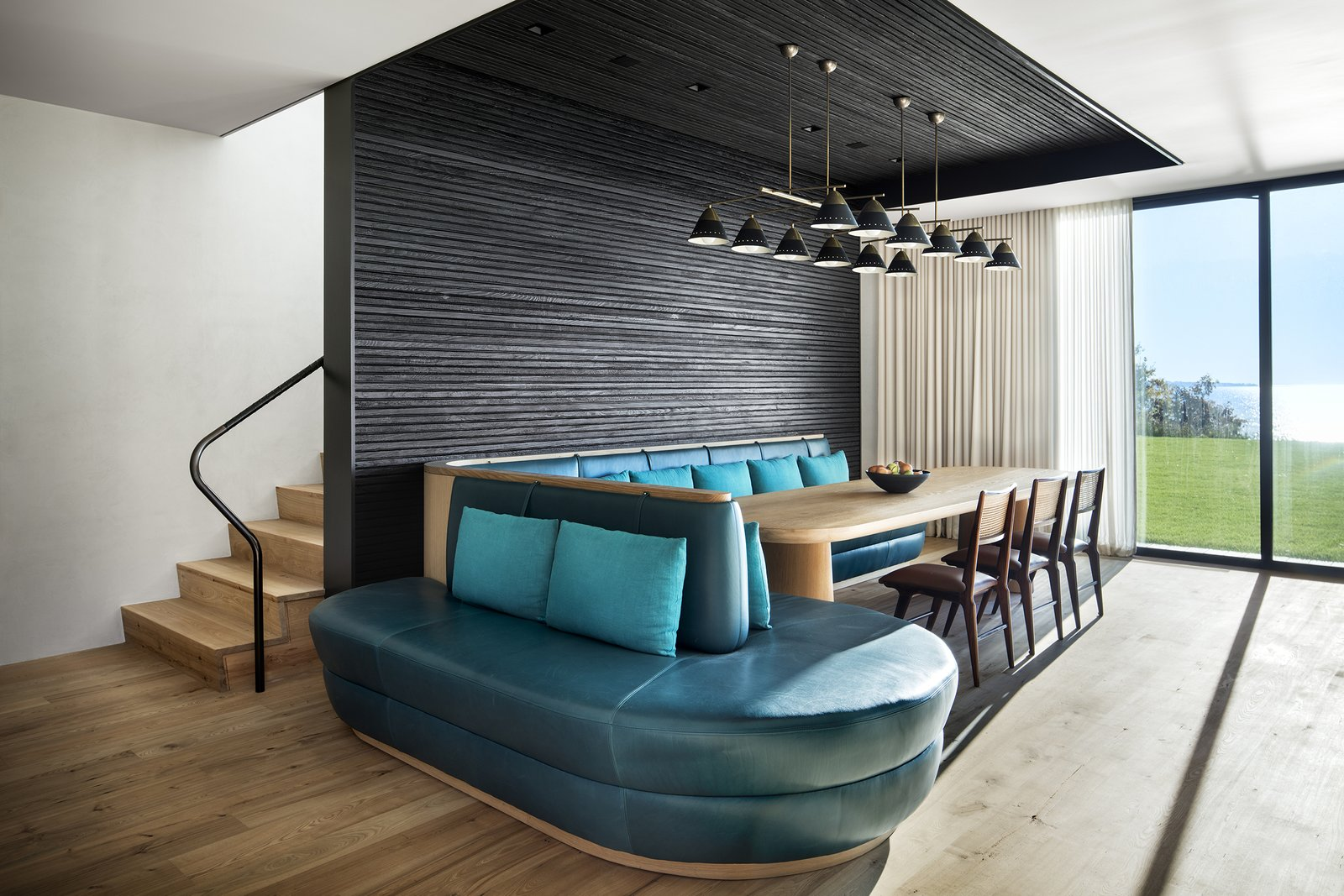 Dining Room, Pendant Lighting, Table, Bench, Light Hardwood Floor, and Chair  Photo 10 of 13 in An Incredible Cedar-Clad House Captures Views of the Sea and Forest